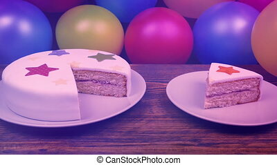 Birthday cake with slice cut out with many balloons around