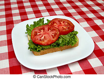 slice of bread, lettuce and tomato - making a blt - one...