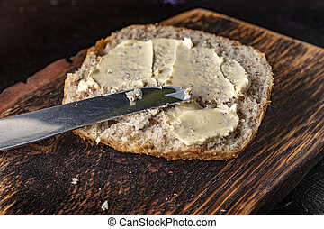 Slice of bread smeared with butter.