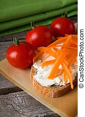 Slice of bread with fresh cheese and carrot shavings