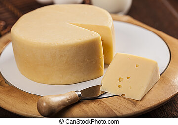 Slice of cheese with a knife on a wooden table.