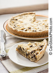 Slice of chicken tart with mushrooms and cheese on a plate