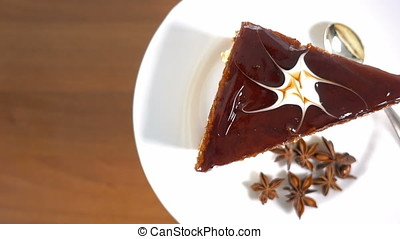 Slice of chocolate cake on white plate rotating, space for...