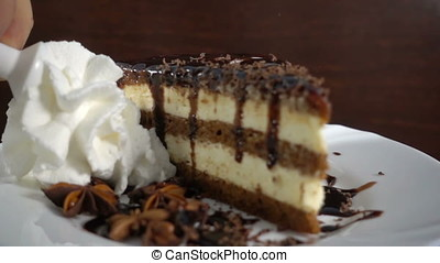 Slice of chocolate cake with anise, whipped cream at 500 fps