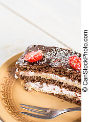 Slice of chocolate cake with fresh strawberries on the plate.