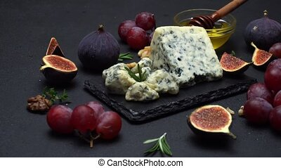 Slice of French Roquefort cheese with figs on stone serving...