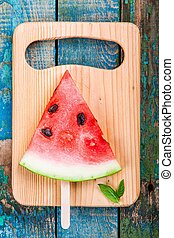Slice of fresh juicy watermelon on a cutting board with mint