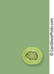Slice of fresh kiwi fruit isolated on a green background.