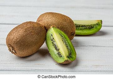 Slice of fresh kiwi fruit on white background