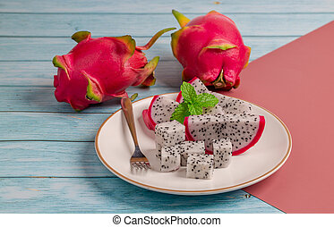 Slice of fresh ripe Dragon fruit with mint on white plate for dessert on blue wooden table