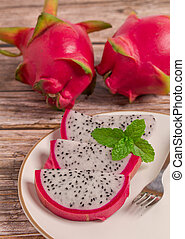 Slice of fresh ripe Dragon fruit with mint on white plate for dessert on wooden table