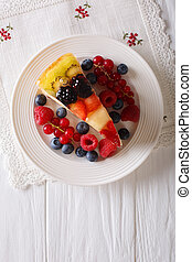 Slice of fruit jelly cake closeup on a plate. vertical top view