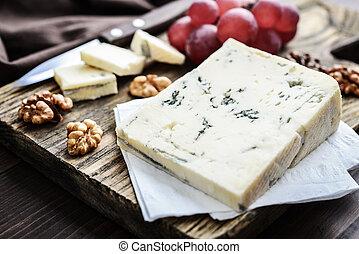 Slice of Gorgonzola cheese on cutting board