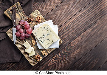 Slice of Gorgonzola cheese on cutting board served with ...