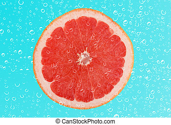 Slice of grapefruit with drop on blue background