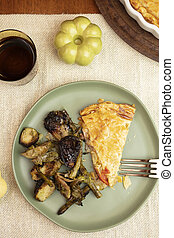 Slice of Ham and Cheese Tart Pie served with brussel sprouts and asparagus in a dinner setting