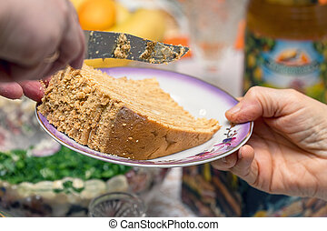 Slice of homemade delicious honey cake with nuts on saucer
