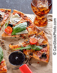 Slice of homemade Rustic pizza with bacon, tomatoes, olives and basil