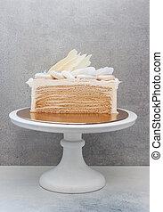 Slice of layered honey cake decorated with chocolate