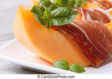 slice of melon wrapped in prosciutto on a plate macro