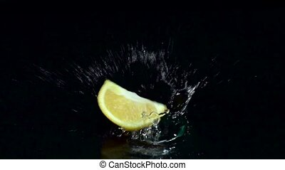 Slice of orange falls into the water. Black background. Slow motion