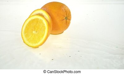 Slice of orange falls into the water . White background. Slow motion