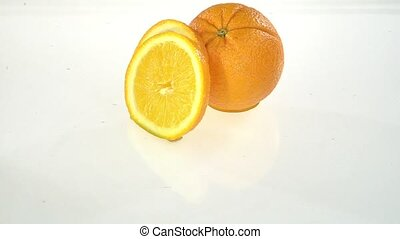 Slice of orange falls into the water . White background....