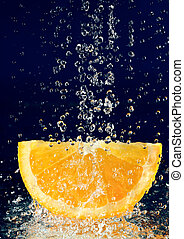 Slice of orange with stopped motion water drops on deep blue
