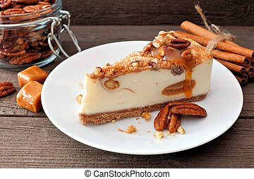 Slice of pecan caramel cheesecake on plate with a rustic wood background