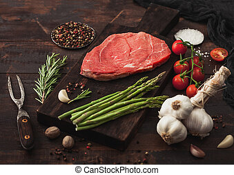 Slice of raw fresh beef braising steak on chopping board with garlic, asparagus and tomatoes with salt and pepper with rosemary and meat fork on wood.