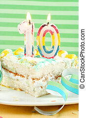 slice of tenth birthday cake with lit candle, confetti, and...