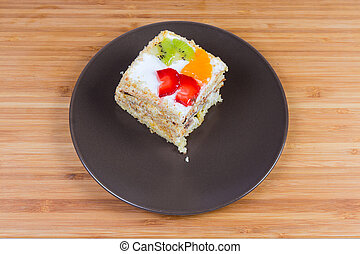 Slice of the layered sponge cake with fruits decoration