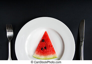 slice of watermelon on a white plate on a black background with a knife and fork