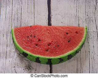Slice of watermelon on a white wooden background