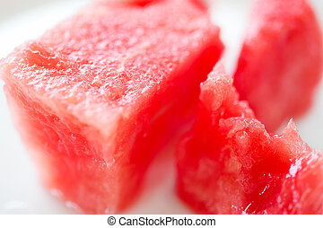 Slice of watermelon on white plate, close up photo