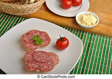 slice poppy seed bread with salami on a plate