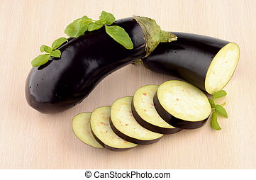 Sliced aubergine, eggplant with basil leaves on bright wooden table