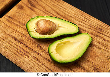 Sliced avocado on a wooden background.