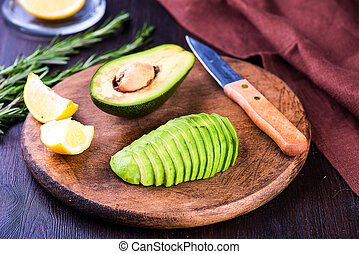 Sliced avocado with knife on cutting board