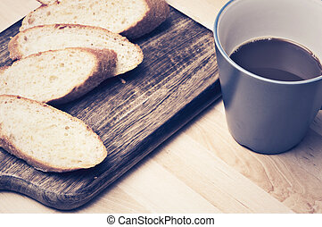 Sliced baguette bread on wooden plate with coffee