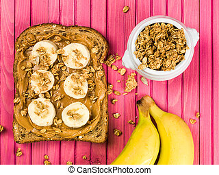Sliced Banana and Peanut Butter on Wholegrain Toast Against a Pink Background