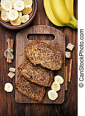 Sliced banana bread on wooden cutting board, top view