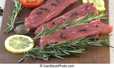 Sliced beef on cutting board with Rosemary