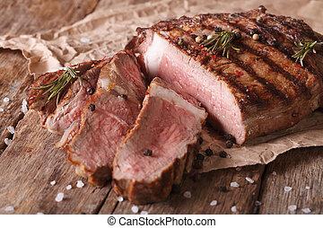 sliced beef steak medium on an old table. Horizontal close-...