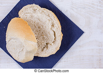 Sliced bread on the blue napkin over wooden background