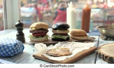 Sliced burger bun on board. Hand holding mayonnaise bottle....