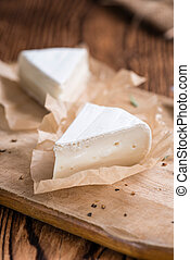 Sliced Camembert (close-up shot) on rustic wooden background