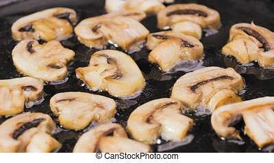 Sliced champignon mushrooms are fried in a hot pan in close up. Golden slices of champignons are fried in olive oil. Preparing vegetables for cooking dinner. Beautiful wallpaper of cooking for restaurant. Slow motion