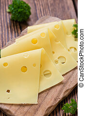 Sliced Cheese (close-up shot) on vintage wooden background