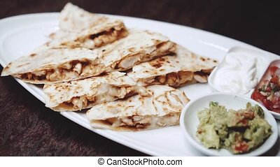 Sliced chicken and cheese quesadilla served with guacamole, ...